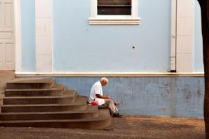 man on steps of church
